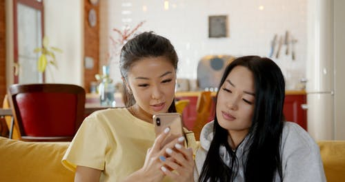 A Woman Showing Another Woman Her Phone
