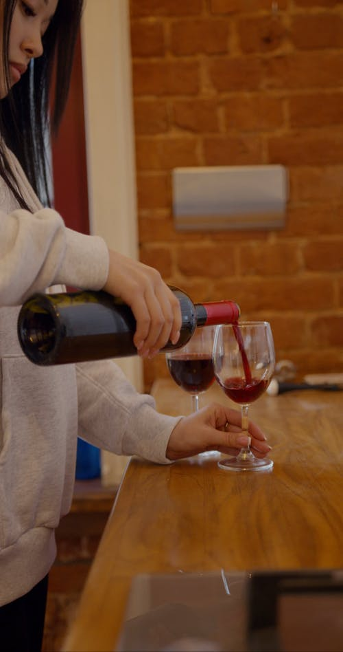 A Woman Pouring Red Wine On Glasses