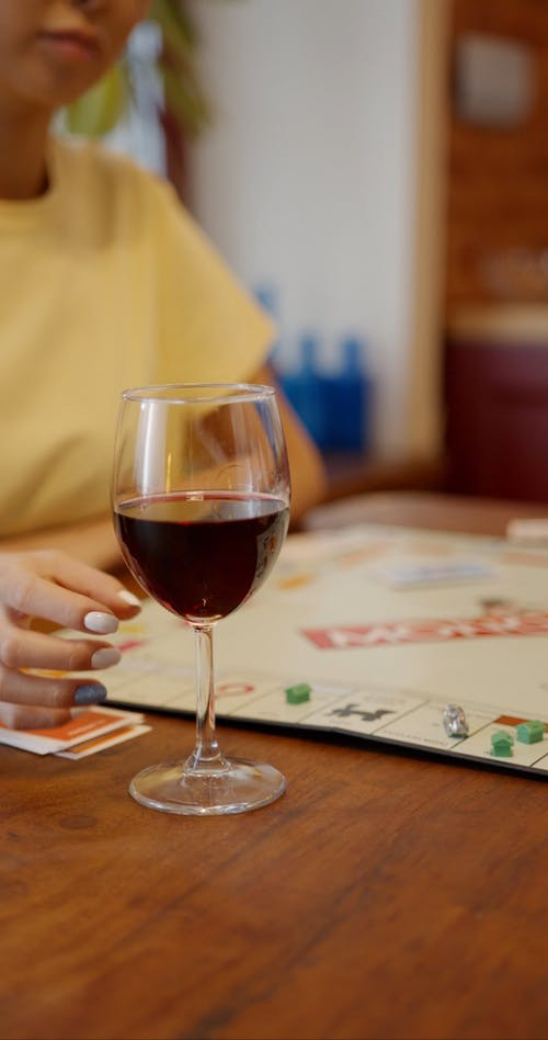 A Woman Drinking Red Wine While Playing A Game Of Monopoly