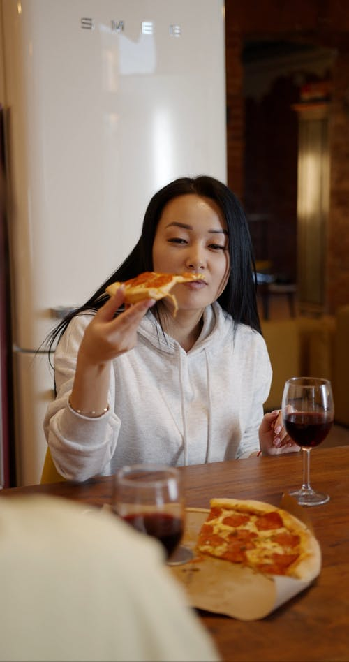 A Woman In White Hoodie Sweat Shirt Eating A Slice Of Pizza