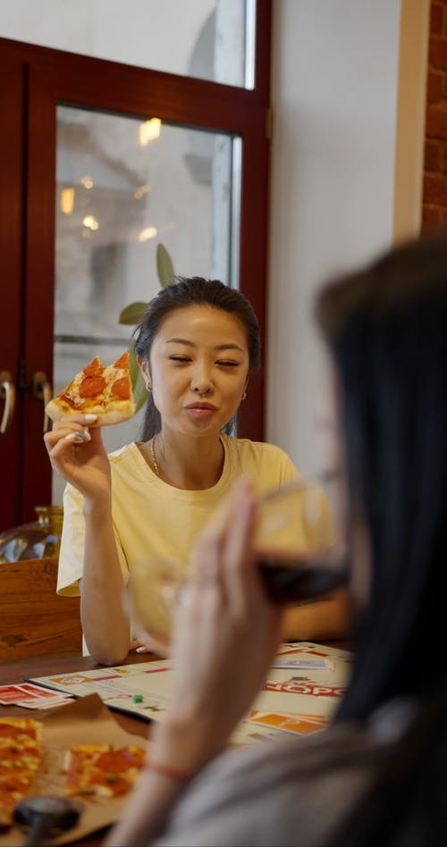 Two Women Eating Pizza With Red Wine While Playing A Game Of Monopoly