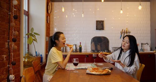 Two Women Enjoy Eating A Pizza With A Glass Of Red Wine