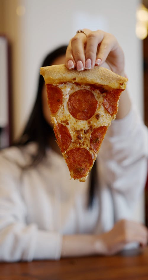 A Woman Eating A Slice Pepperoni Pizza