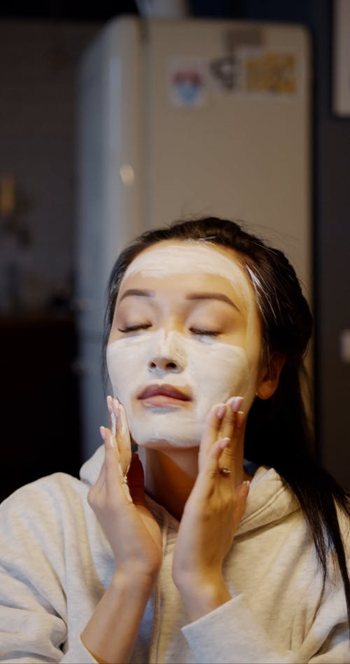 A Young Woman In Sweat Shirt Applying Cosmetic Facial Cream On Her Face