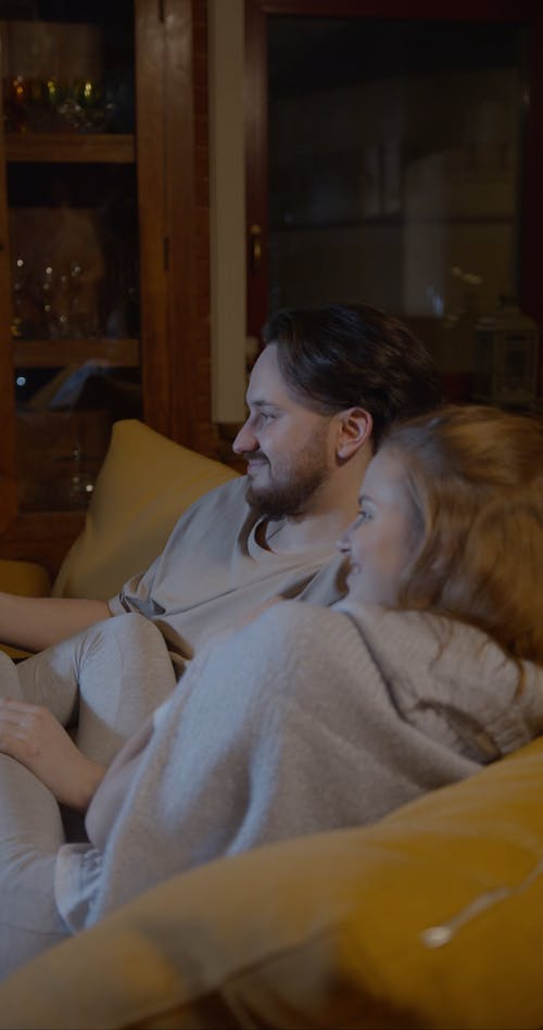 A Couple Sharing Smiles While Watching Television In Their Living Room