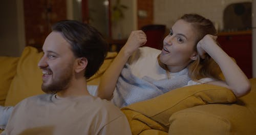 A Couple Having A Good Time Watching Television While At Home