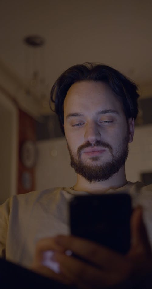 A Man Using His Cellphone With His Wife Peeking Behind