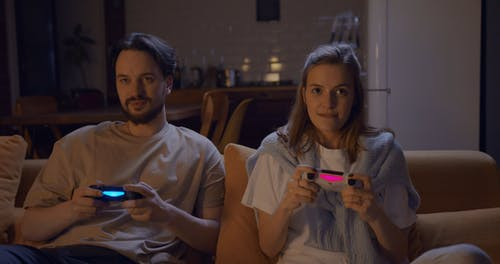 A Couple Playing A Game Console Using Wireless Remote Controls
