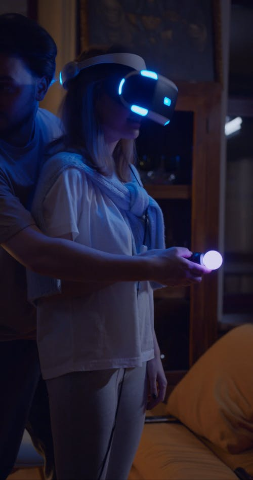 A Man Assisting His Wife In Playing A Virtual Reality Game