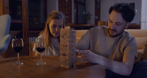 A Couple Playing A Game Of Jenga While Staying At Home