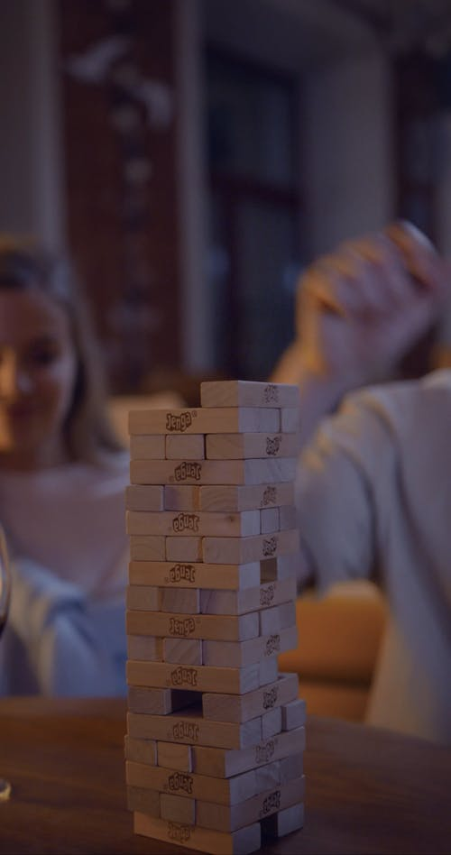 A Couple Playing A Game Of Jenga At Home