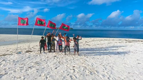 Local People Standing In Front Of Maldives Flag Planted In The Beach