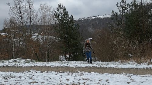 A Woman Walking On A Forest Trail In Winter