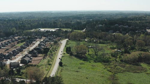 Drone Footage Of A Town With Green Fields And Trees