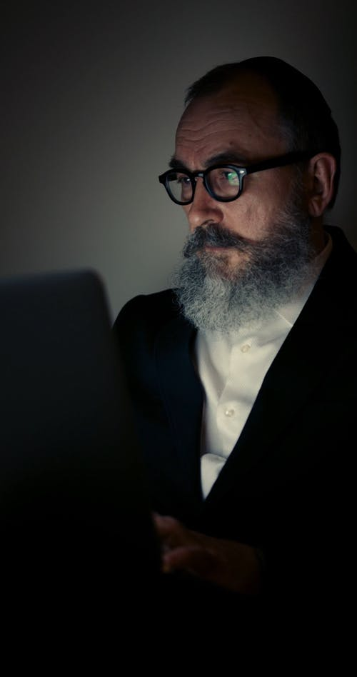 A Man Wearing Eyeglasses Working With A Laptop