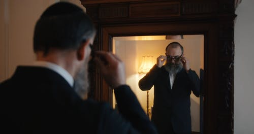 A Man Grooming In Front Of A Mirror