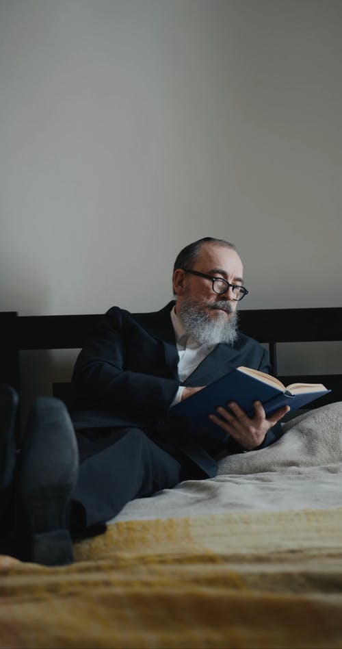 A man Reading A Book While Resting On A Bed