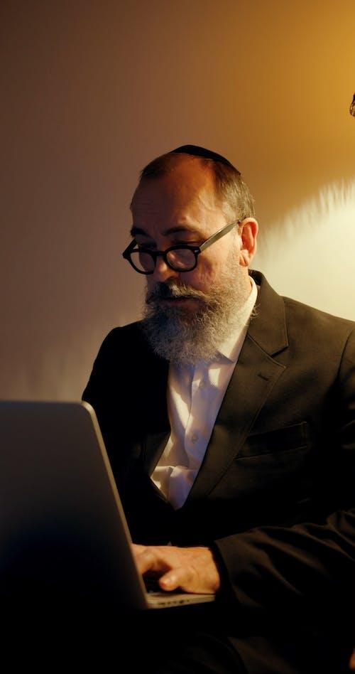 An Elderly Jewish Man Using A Laptop
