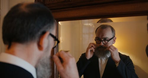 An Jewish Grooming His Moustache And Wearing His Kippah Looking At A Mirror