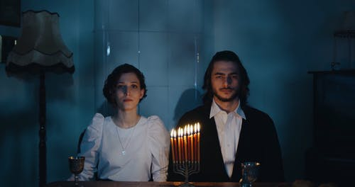 A Couple Seated Behind The Burning Candles Of The Hanukkiah