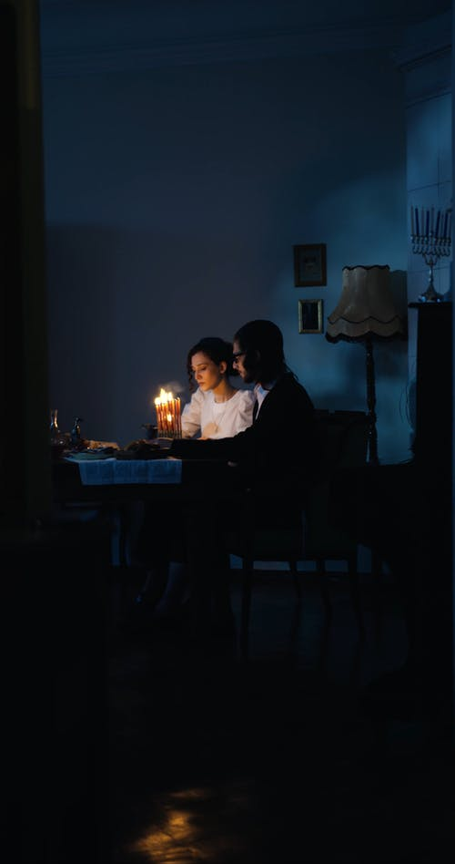 A Couple Lighting Up Candles
