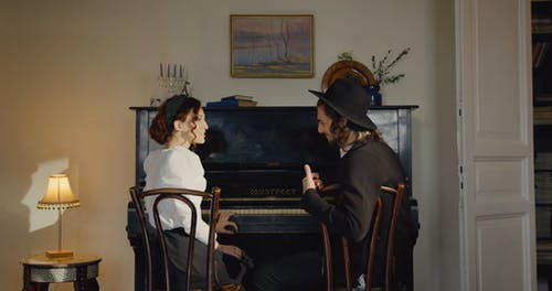A Jewish Couple Sitting In Fron Of The Piano