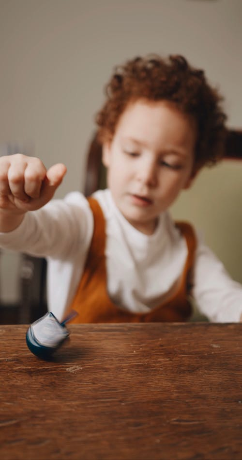 A Boy Playing A Spinning Top Over The Dining Table