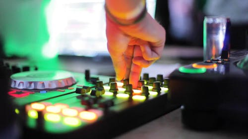 Close-Up View of a Person Using a DJ Mixer