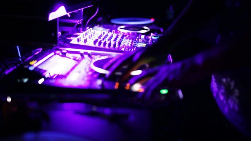 A Person Using His DJ Mixer Under the Purple Light