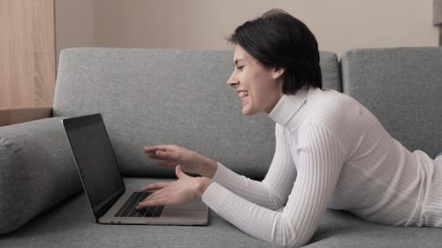 A Woman Communicating Via Video Call On Her Laptop