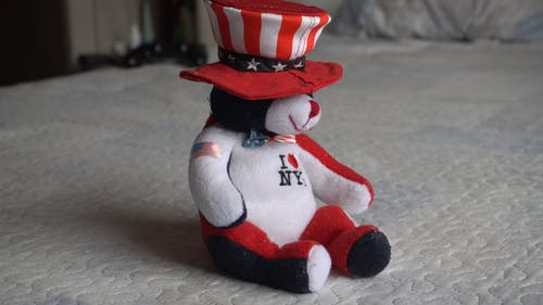 A Stuffed Teddy Bear In American Flag Colors