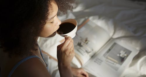 A Woman Reading A magazine While Having Coffee In Bed