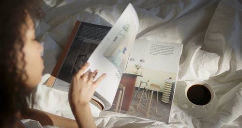 A Woman Having Coffee In Bed While Looking At A Magazine