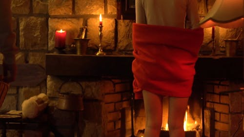 A Standing Couple Embracing Each Other In Front Of The Fireplace