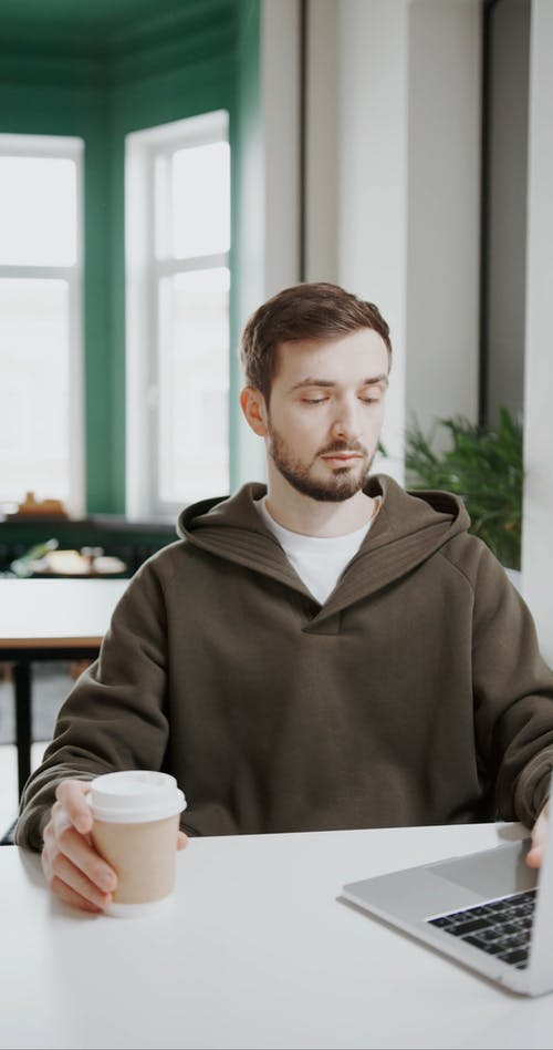 A Man Working On His Laptop While Drinking Coffee