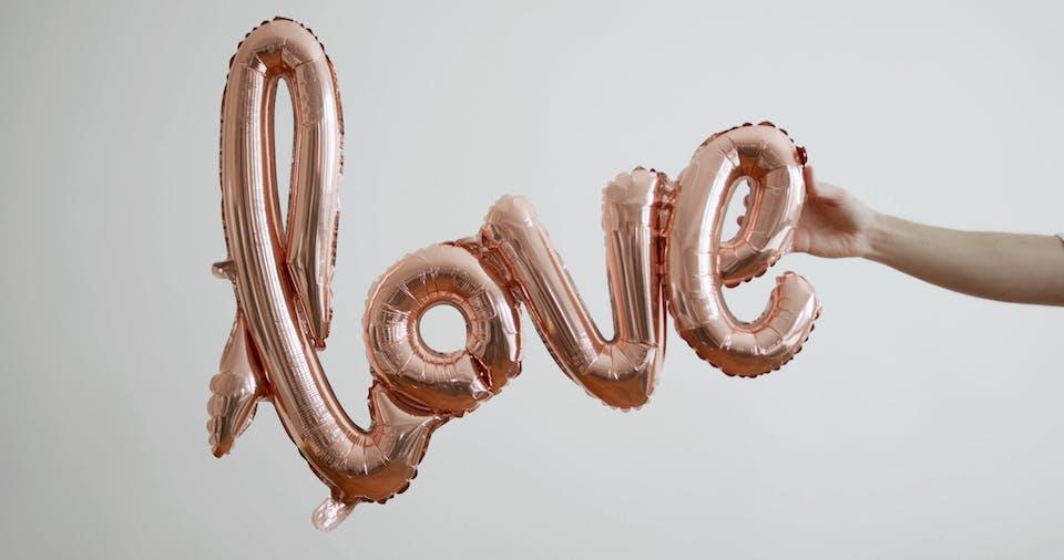 A Person Holding A Love Balloon