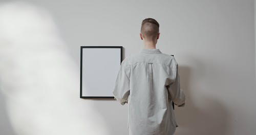 A Man Hanging A Picture Frame On A Wall