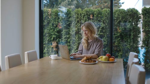 Woman Eating an Apple and Working From Home