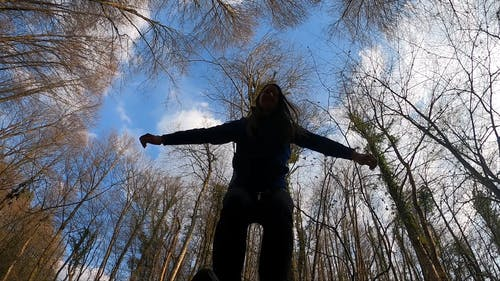 A Woman Jumping From The Base Of A Cut Tree