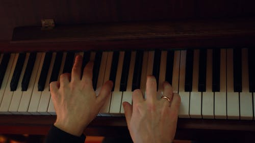 A Person Wearing A Wedding Ring Playing A Piano