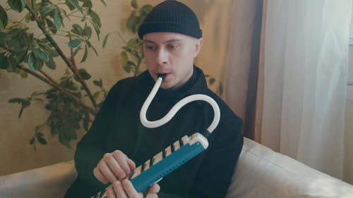 A Man Playing A Melodica