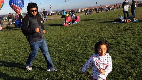 A Family Enjoying Their Day Playing And watching The Hot Air Balloons Festival