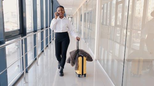 Woman Walking in a Corridor While Having a Phone Call