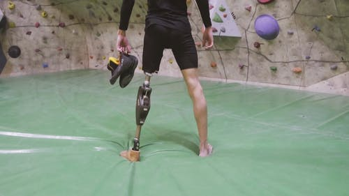 Man With Prosthetic Leg Standing In Front Of A Rock Climbing Wall