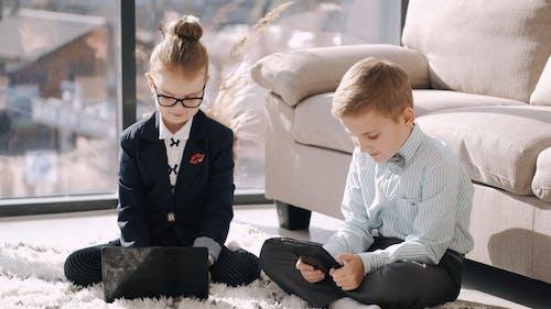 Kids In Formal Wear Using Electronic Gadgets