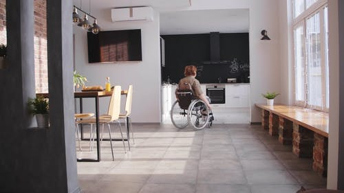 A Woman in a Wheelchair Pushing Herself to get the Coffee Maker