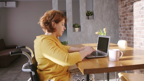 A Woman on a Wheelchair Typing in her Laptop