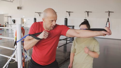 A Boxing Trainer Showing A Woman How To Use  A Resistance Band