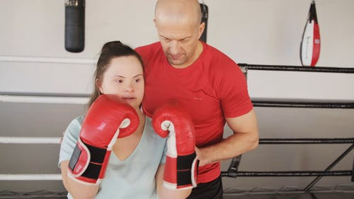 A Boxing Trainer Teaching A Woman How To Punch