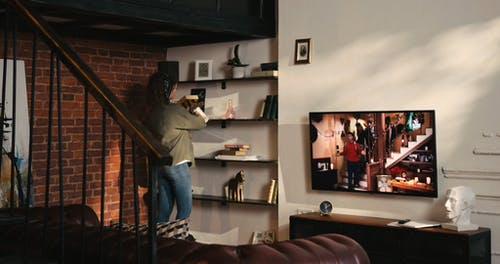 A Woman Taking a Break From Cleaning To Watch Television